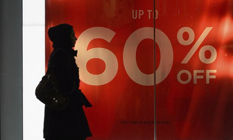 A shopper passes a sale sign on Oxford Street in London with only a week left until Christmas